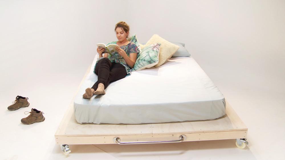 Para darle una sensación de amplitud al dormitorio haremos esta cama baja de dos plazas, que al tener menos volumen agranda el campo visual y permite a su vez una mayor luminosidad. Le pondremos ruedas y una manilla para que sea fácil de manipular cuando queramos limpiar o simplemente cambiarla de lugar.