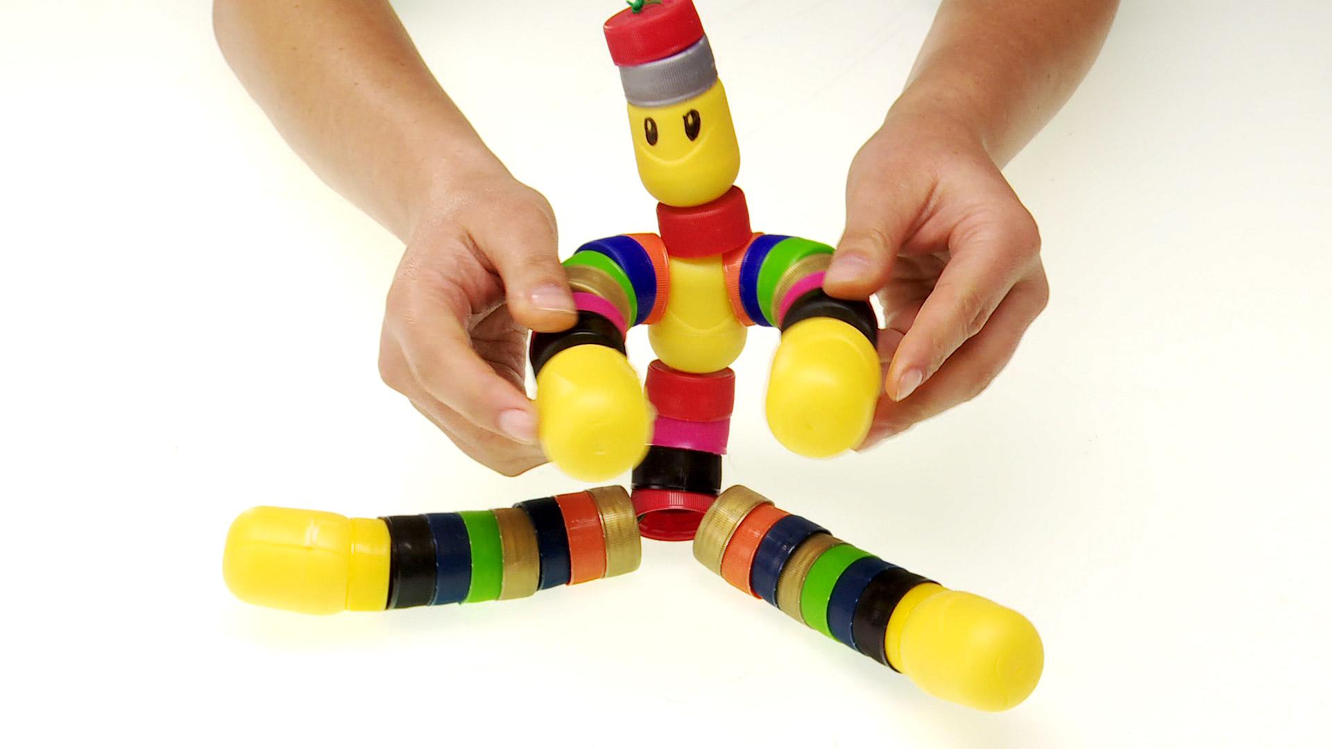 No solo reciclando podemos darle otro uso a las tapas roscas de bebida, también se pueden reutilizar, y con un poco de creatividad hacer un colorido y entretenido muñeco flexible.