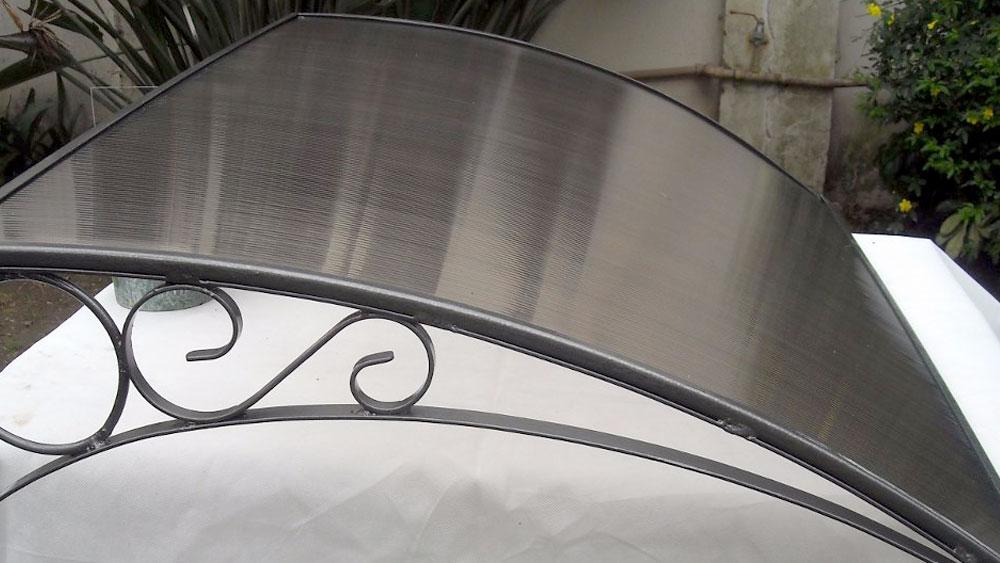 Una buena solución para proteger ventanas o puertas de la lluvia y el exceso de sol es instalar un alero. Una estructura que va fija al muro y que sirve de techo. Hay muchas alternativas de materiales y formas, pero por ser liviano y fácil de instalar es muy recomendable un alero de policarbonato con soportes plásticos.