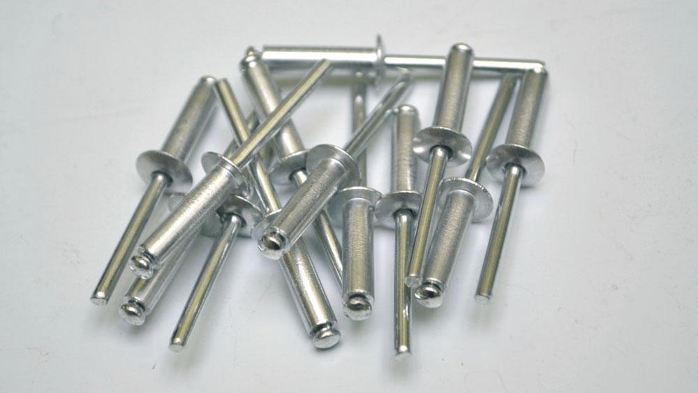 """El remache ciego, más conocido como remache """"pop"""", permite fijar dos elementos, cuando uno de ellos no deja accesible ninguna de sus caras. Se compone de un cuerpo con cabeza de collarín, fabricado con una aleación deformable y de una varilla que tiene un extremo abultado. Este tipo de remache es muy usado por ejemplo para instalar las placas de las patentes de los vehículos. Aunque el remache """"pop"""" permite unir dos piezas de manera rápida y duradera, son factibles de ser extraídos, sólo siguiendo un par de sencillos pasos."""